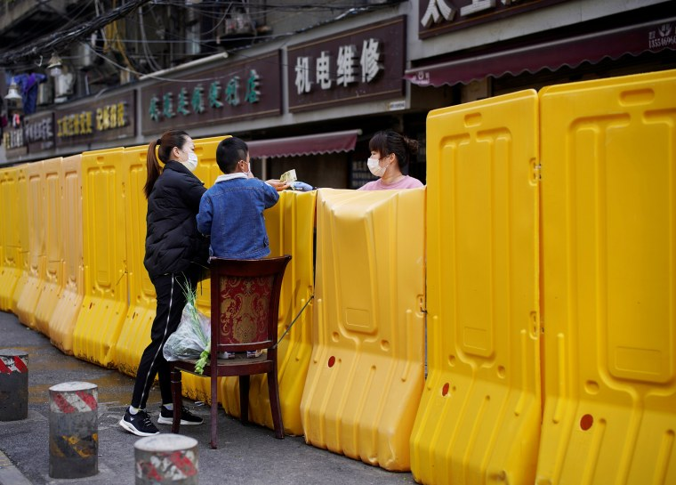 Image: Woman pays for vegetables over barriers set up to block buildings from a street in Wuhan