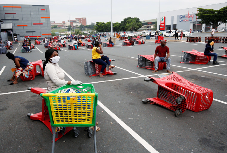 Image: Shoppers queue at a grocery store during a nationwide 21 day lockdown in an attempt to contain the coronavirus disease (COVID-19) outbreak in Chatsworth near Durban