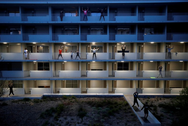 Image: Residents exercise on their balconies following fitness trainers in Nantes