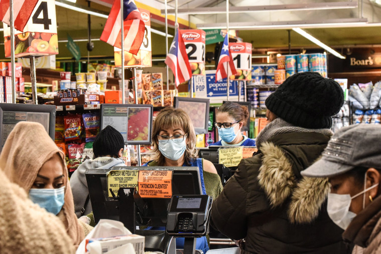 Image: Cashiers wearing protective masks work in a grocery store in the Bushwick neighborhood of Brooklyn  on April 2, 2020 in New York City.