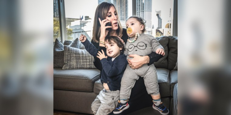 """MSNBC anchor and """"Morning Joe First Look"""" co-anchor Yasmin Vossoughian on the phone while holding her sons Azur and Noor."""