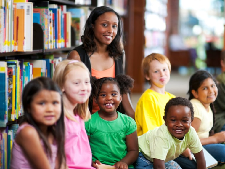 Teacher with diverse group of elementary students in school library