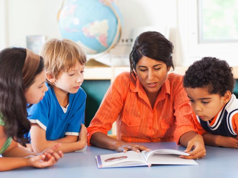 Teacher teaches young students.