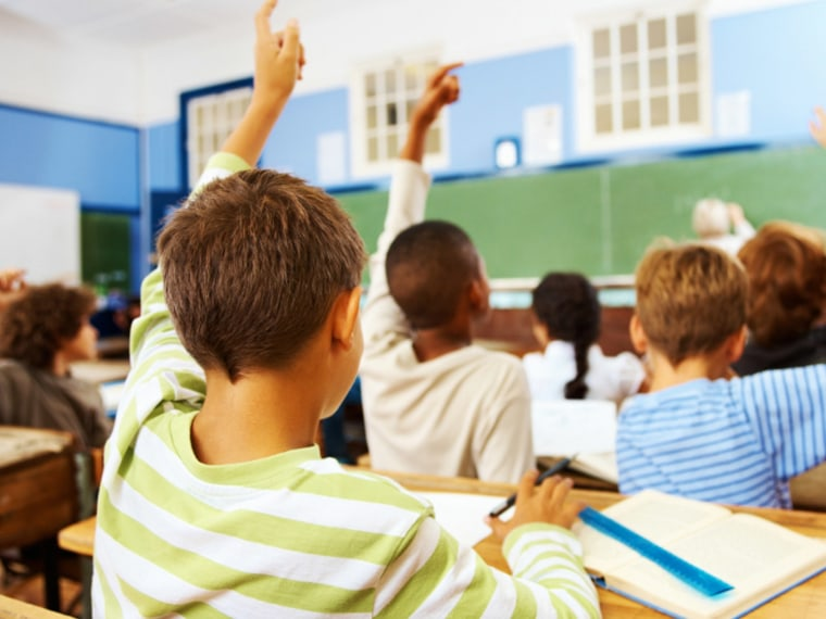 Students in classroom raise hands.