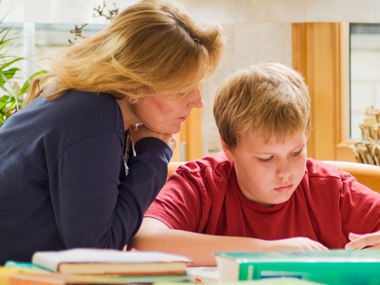 Mother helps son with homework.