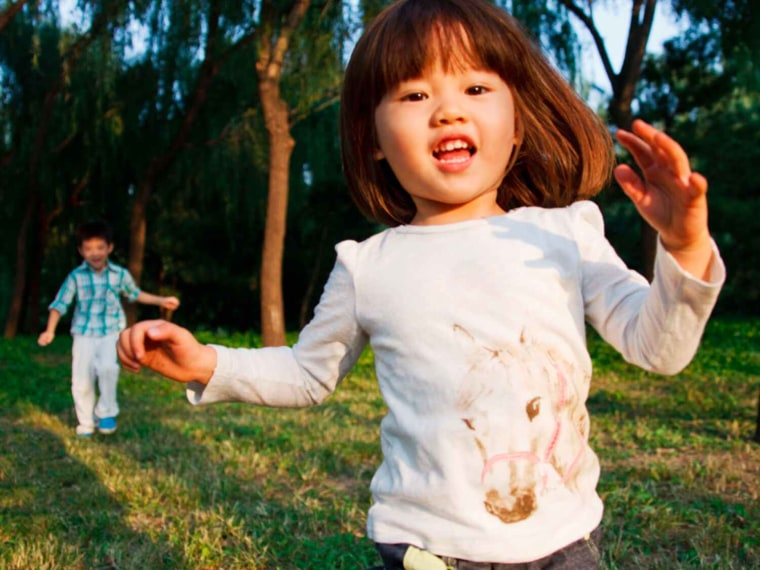 Happy brunette child in horse shirt runs outside away from boy