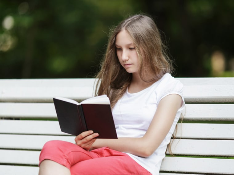 A student reads a book on a bench.