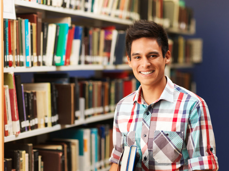 A student stands in a library.