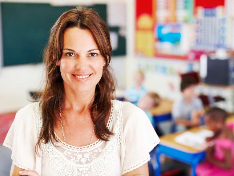 A teacher smiling in a classroom.