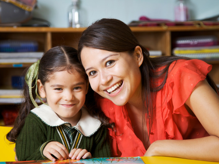 Teacher smiles with young student.