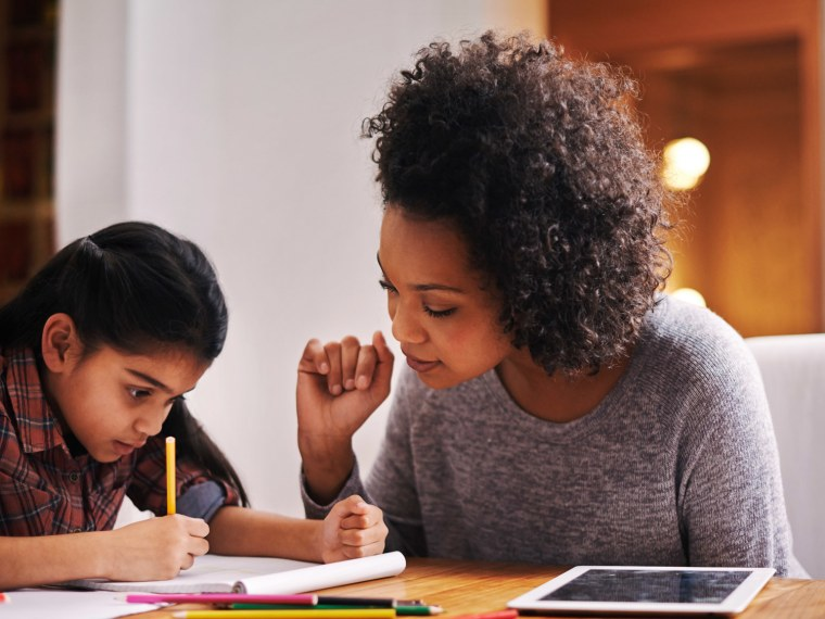 Mother helps daughter with homework.