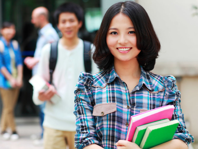 A smiling student holds textbooks.