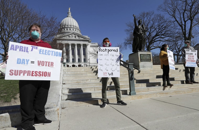 Image: A group with C.O.V.I.D., Citizens Outraged Voters in Danger, including, from left, Ron Rosenberry Chase and Jim O'Donnell, protest while wearing masks outside the State Capitol during a special session regarding the spring election in Madison, Wis
