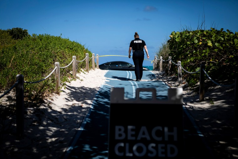 Image: A police officer walks toward a closed portion of South Beach, Fla., on March 19, 2020.