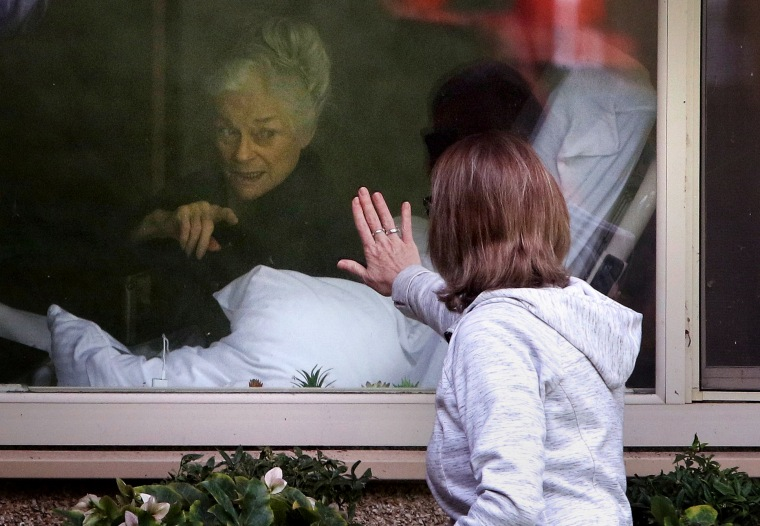 Image: Lori Spencer visits her mother, Judie Shape, who tested positive for coronavirus at the Life Care Center of Kirkland nursing home near Seattle, on March 11, 2020.