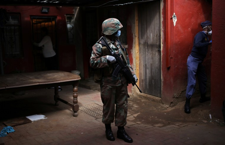Image: A Soldier and a member of the South African police service search a house