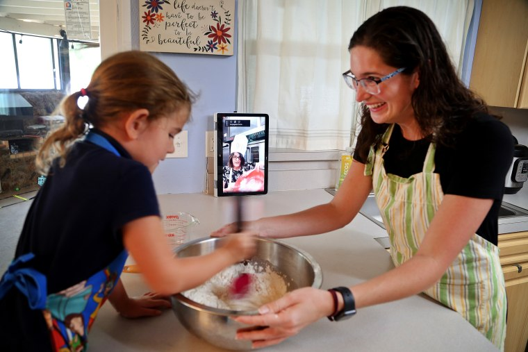 Image: Sarah Cowart, 6, helps her mother, Hana Cowart, mix dough to make matzo while watching a YouTube live video by Maureen Seehan, a director of learning at Congregation B'nai Israel of St. Petersburg, Fla., on March 31, 2020.