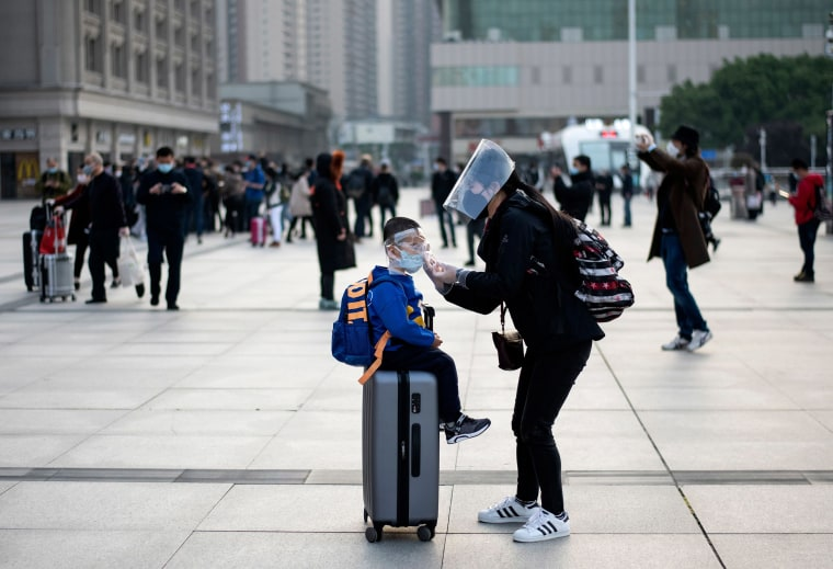 Image: A woman wearing a face mask adjusts her child's mask as they arrive at Hankou Railway Station in Wuhan to take one of the first trains leaving the city in China's central Hubei province