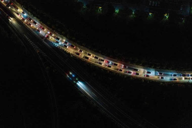 Image: Cars queuing at a highway toll station in Wuhan in China's central Hubei province, as they prepare to leave the city after authorities lifted a more than two-month ban on outbound travel