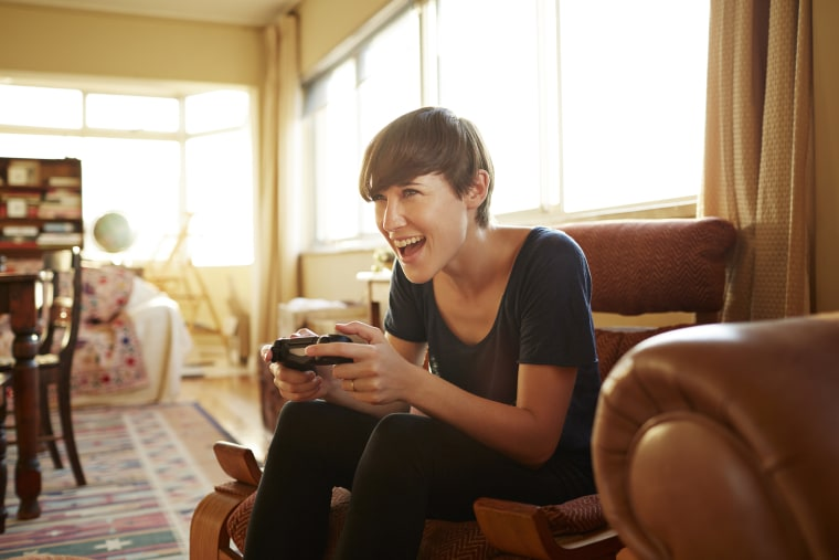 Image: Young woman playing on gaming console at home