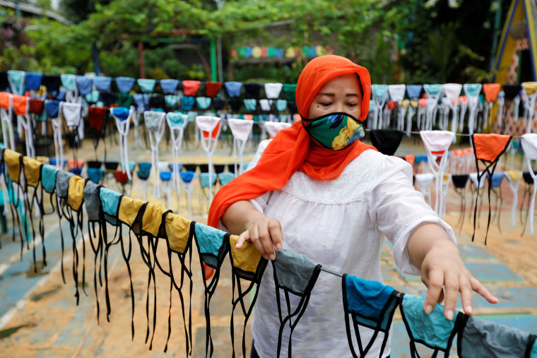 Image: A woman puts cloth face masks on a string to dry before distributing it for free around the neighbourhood, amid the spread of coronavirus disease (COVID-19) outbreak, in Tangerang, on the outskirts of Jakarta, Indonesia