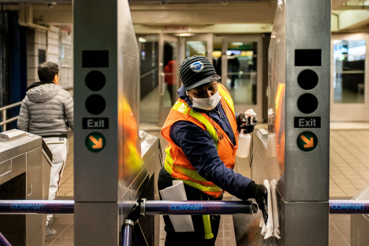 Image: FILE PHOTO: An MTA transit worker cleans a nearly empty Times Square - 42nd street subway station following the outbreak of coronavirus disease (COVID-19) in New York City