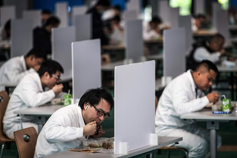 Employees eat lunch at a Dongfeng Honda auto plant in Wuhan, China, on April 7.