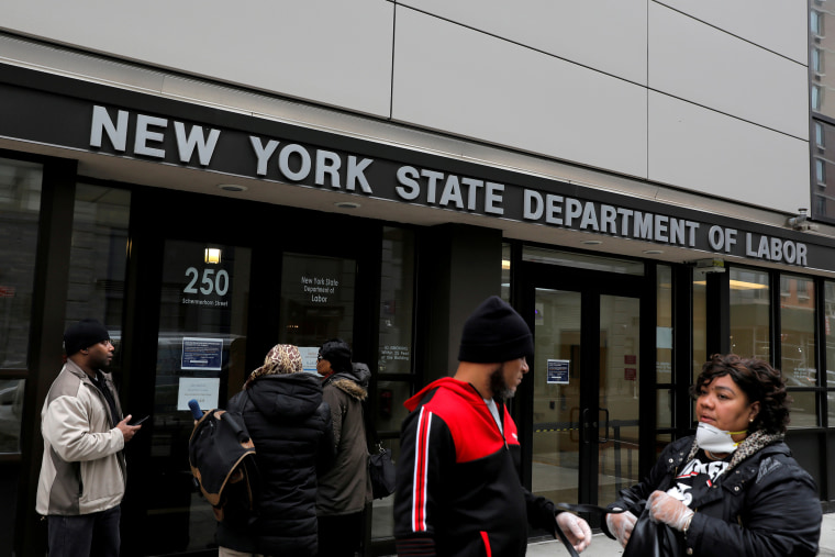Image: People gather at the entrance for the New York State Department of Labor offices, which closed to the public due to the coronavirus disease (COVID-19) outbreak in the Brooklyn borough of New York City