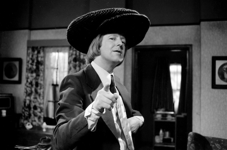 "Image: Tim Brooke-Taylor in an episode of the BBC series ""The Goodies\"" in 1975."