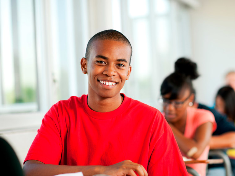A student smiles in a classroom.