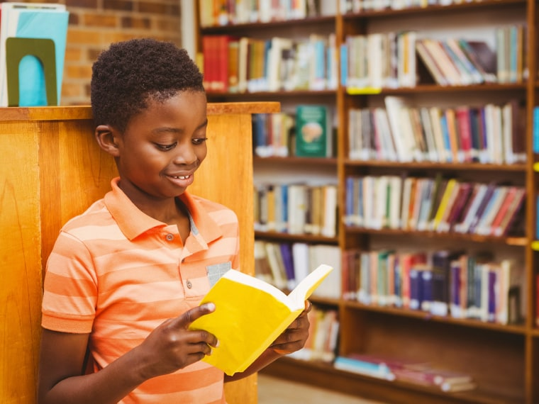 Young student reads in a library.