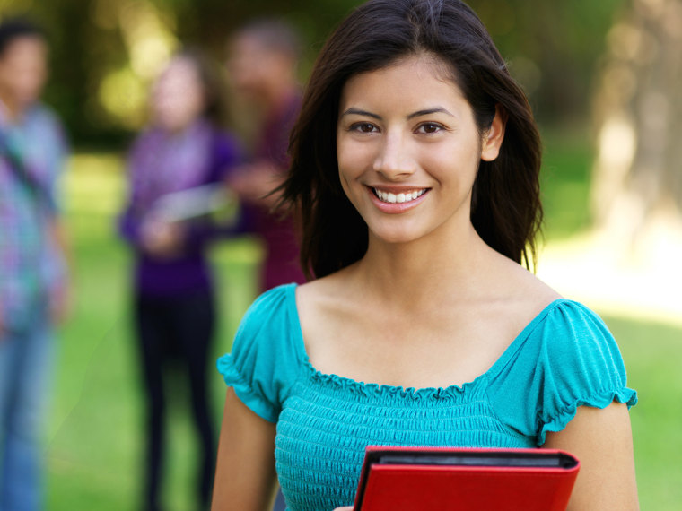 Teen girl smiles while holding her notebooks