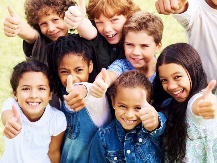 Group of elementary students smiling giving a thumbs up