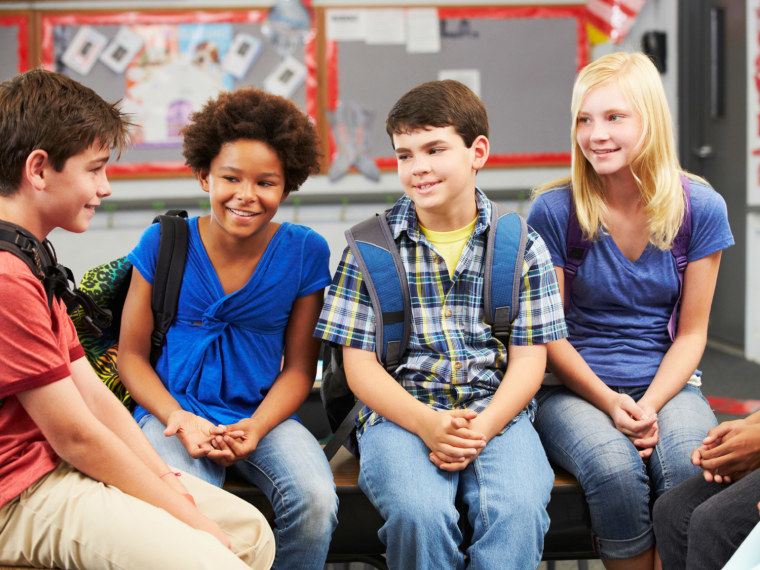Four middle schoolers talk in a classroom