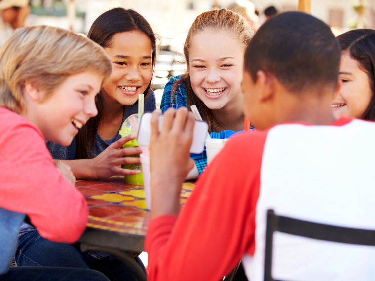 Group of middle schoolers look at a phone screen at lunch