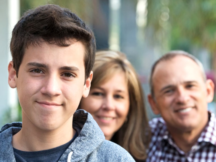 Young teen in hoodie looking at camera with parents behind him