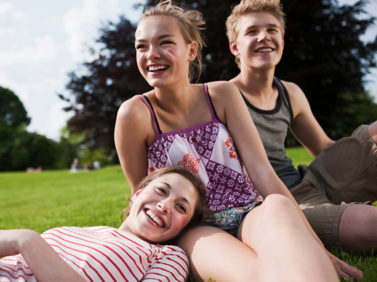 Teens sitting outside hanging out with girl laying her head on her friends lap