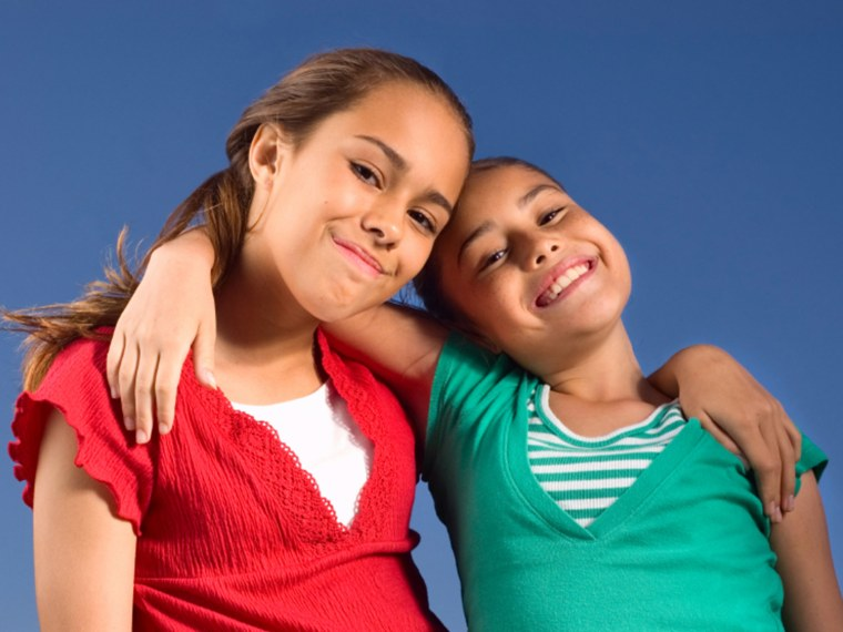 Two young girls wrap their arms around each other