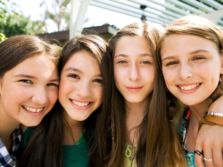 Four Middle School girls smiling at camera hanging out