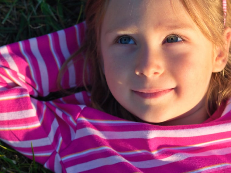 Little girl day dreams in the grass