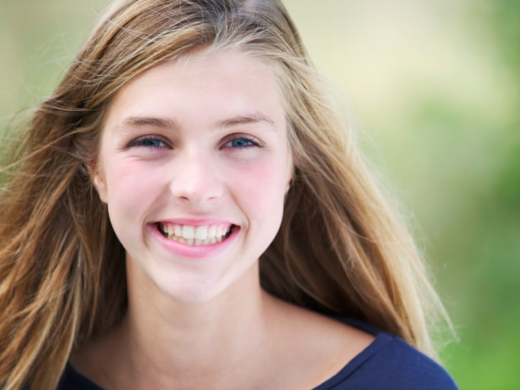 Teen blue eyed girl smiling into camera close up