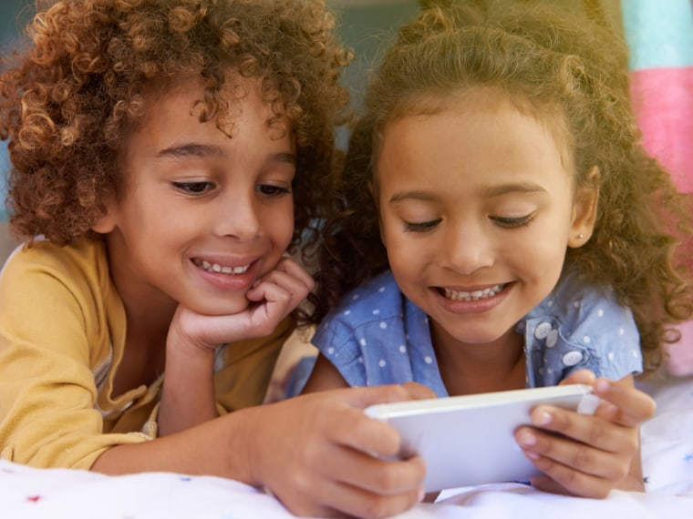 Two kids play games on a smart phone