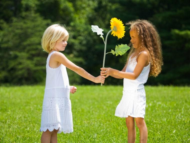 Two girls share a sunflower