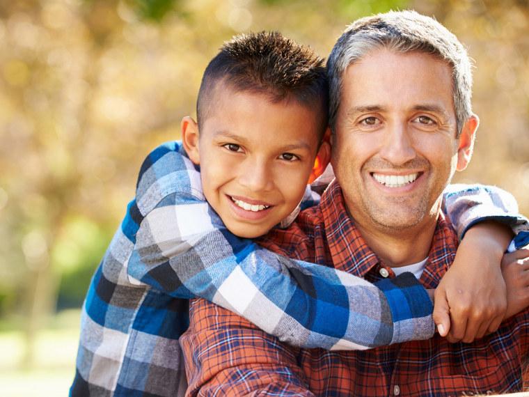 Father and young son hug