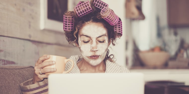 Woman With Hair Curlers Using Laptop On Sofa At Home