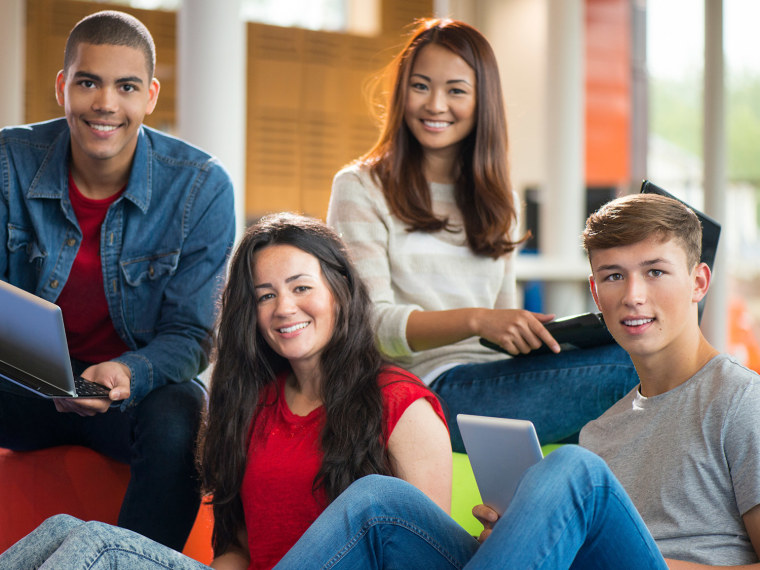 Diverse group of teens hanging out at school