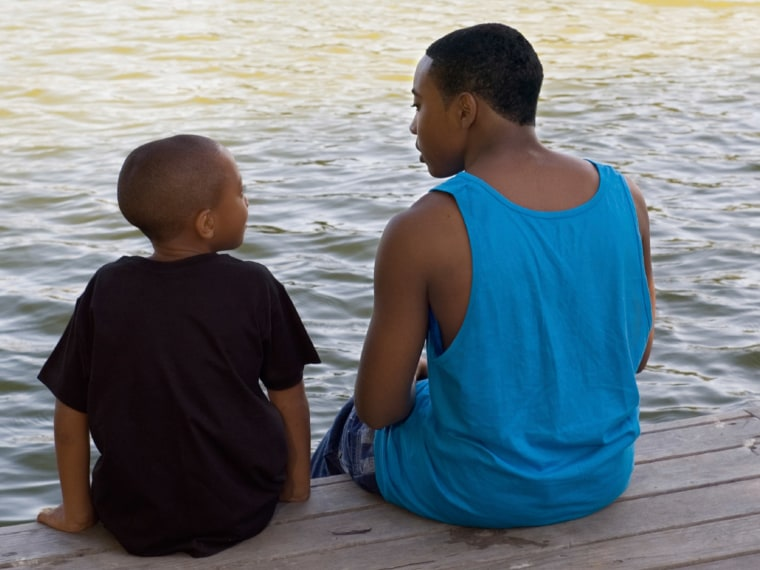 Teen sitting with sibling on a dock talking