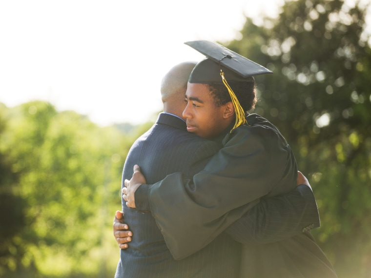 Father hugging high school son who just graduated