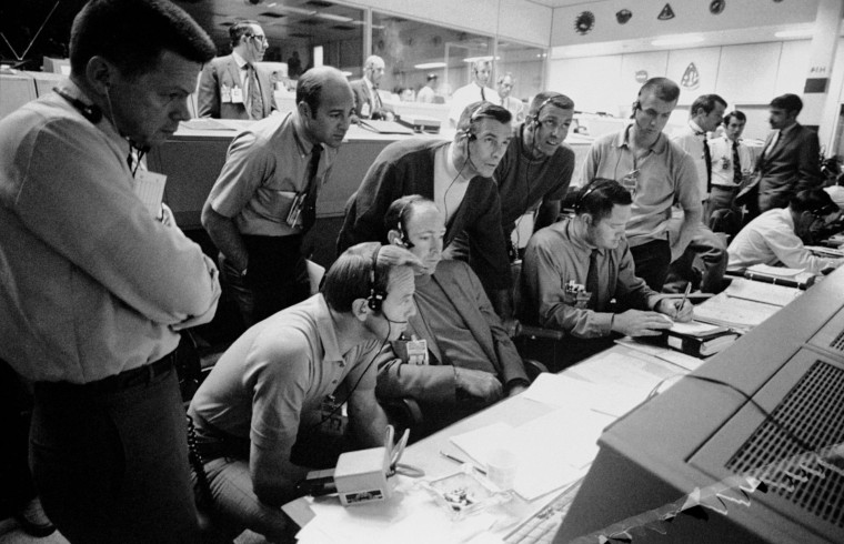 S70-34986 (14 April 1970) --- A group of six astronauts and two flight controllers monitor the console activity in the Mission Operations Control Room (MOCR) of the Mission Control Center (MCC) during the problem-plagued Apollo 13 lunar landing mission. Seated, left to right, are MOCR Guidance Officer Raymond F. Teague; astronaut Edgar D. Mitchell, Apollo 14 prime crew lunar module pilot; and astronaut Alan B. Shepard Jr., Apollo 14 prime crew commander. Standing, left to right, are scientist-astronaut Anthony W. England; astronaut Joe H. Engle, Apollo 14 backup crew lunar module pilot; astronaut Eugene A. Cernan, Apollo 14 backup crew commander; astronaut Ronald E. Evans, Apollo 14 backup crew command module pilot; and M.P. Frank, a flight controller. When this picture was made, the Apollo 13 moon landing had already been canceled, and the Apollo 13 crew men were in trans-Earth trajectory attempting to bring their damaged spacecraft back home.