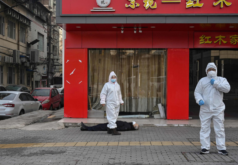 Image: Officials in protective suits check on an elderly man who collapsed and died on a street near a hospital in Wuhan